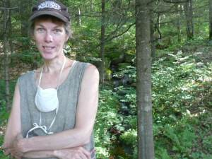 Linda standing near some trees. Shes' wearing a cap and has a mask dangling loosely from her neck.